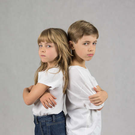 Young boy and girl siblings standing and leaning against each other back with crossed hands with serious faces Lizenzfreie Bilder