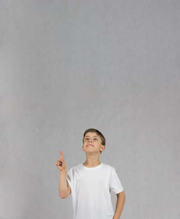 Young boy wearing white t-shirt smiling and looking up with his hand and figer up like having an idea
