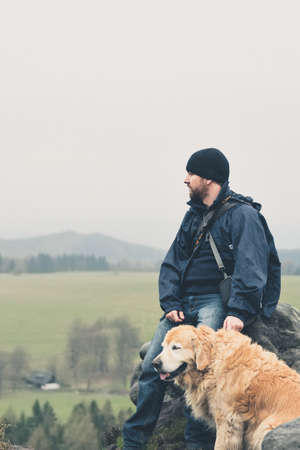Young man wearing black hat resting on a rock with his dog friend