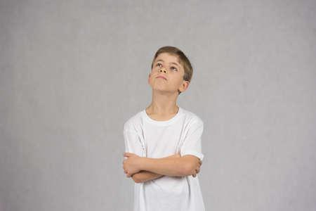 Junge, der weiße T-Shirt trägt, schaut oben mit seinen Händen, die sich überqueren oder über etwas nachdenken