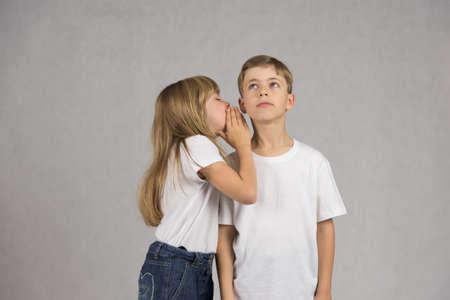 Junges Mädchen flüstern zu ihrem Freund oder Bruder Ohr, beide tragen weiße T-Shirts auf einem grauen Hintergrund isoliert