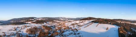 Vogelperspektive auf ein kleines Dorf in Bergen mit Schnee bedeckt in einem sonnigen Wintertag