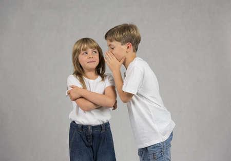 Junger Junge flüstert zu seiner Freundin oder Schwester Ohr, beide tragen weiße T-Shirts auf einem grauen Hintergrund Lizenzfreie Bilder