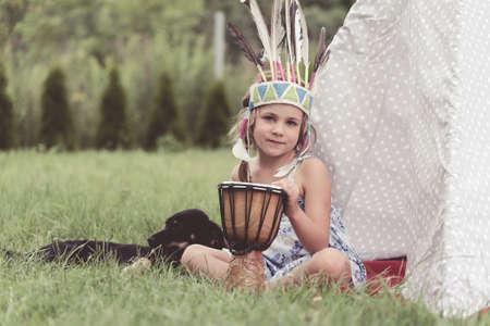 Junges Mädchen mit amerikanischen indischen Constume sitzt mit einer Trommel neben einem Vigvam