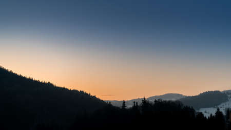 Hügel mit Silhouetten von Bäumen nach Sonnenuntergang