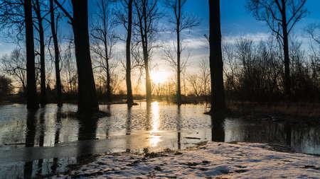 Das Setzen von Sonne, die in einem Fluss an einem kalten Winterabend