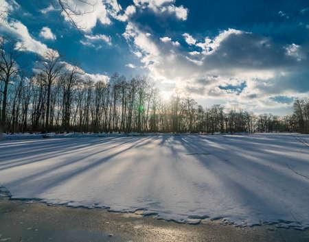 Gefrorener See in einem Park mit Schnee hinter Linie der Bäume Schatten auf der Seeoberfläche Gießen