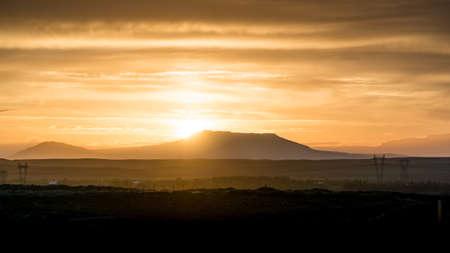 Sonne steigt hinter einem fernen Berg mit Himmel und Clounds mit seinem warmen Licht beleuchtet