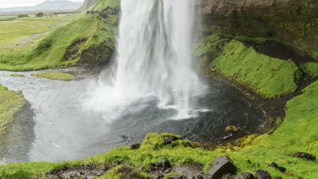 Waters von Seljalandsfoss Wasserfall, der von einem hohen Felsen fällt
