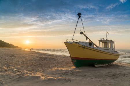 Sonnenuntergang über einem Fischerboot an einem Sandstrand ankern