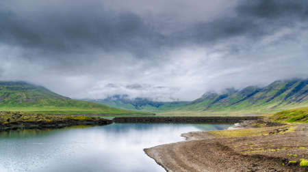 Beautiful icelandic lake surrounded with mountains shrouded in clouds