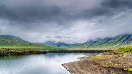 Schöner isländischer See umgeben von Bergen in Wolken gehüllt