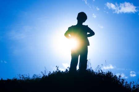 Silhouette eines Jungen auf einem kleinen Hügel, der mit Sonne hinter ihm glänzen