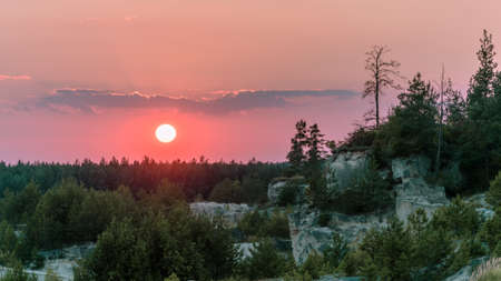 Felsen bedeckt mit Bäumen und Sträuchern bei Sonnenuntergang.