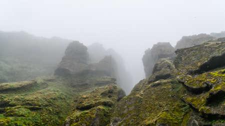 Hohe Felsen bedeckt mit Moos verschwindend im dicken Nebel