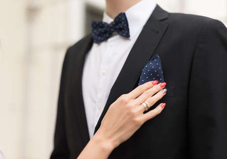 A close up shot of a hand of a bride setting a handkerchief in grooms suit pocket