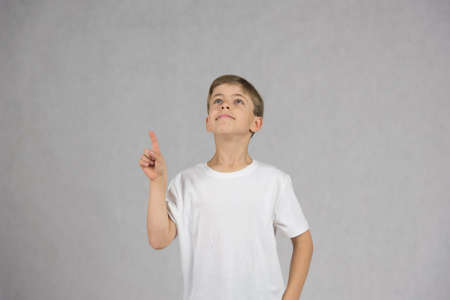 Junge trägt weiße T-Shirt lächelnd und schaut mit seiner Hand und figer wie eine Idee