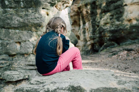 Little sad girl crying sitting on a rock, view from behind Reklamní fotografie