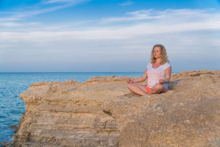 Young attractive woman practicing meditation on a rocky cliff at a sea Reklamní fotografie