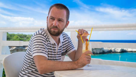 Young handsome man having a fancy colorful cocktail drink at a sea side restaurant
