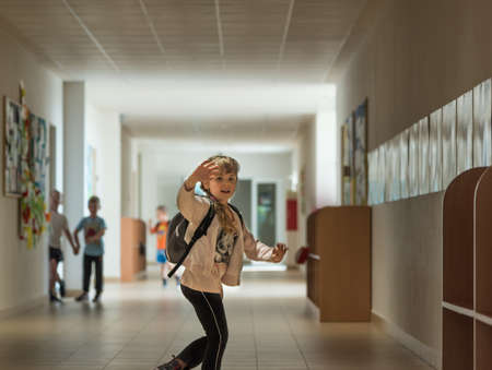 Little girl weaving to her parents while running for her classes over a school corridor Reklamní fotografie - 81432862