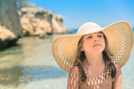 그녀의 밀 짚 모자를 통해 빛나는 햇빛 바다에서 어린 소녀