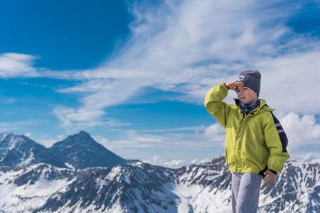 태양으로부터 그의 눈을 덮고 손으로 서있는 높은 산에서 트레킹하는 어린 여행자 소년 스톡 콘텐츠