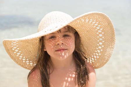Kleines Mädchen auf See mit Sonnenlicht, das durch ihren Strohhut glänzt Lizenzfreie Bilder