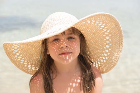 Malá holčička na moři se slunečním světlem zářící kloboukem