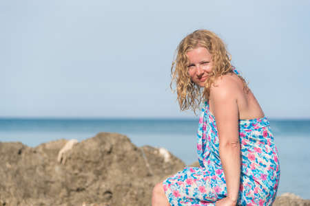 Young long blond hair woman wearing blue dress sitting on rocks at a sea shore and smiling Reklamní fotografie