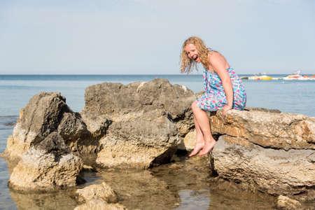 젊은 긴 금발 머리 여자 바위에 앉아서 바다 물로 미끄러 져.