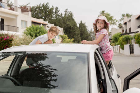 Young children standing out of the car side windows and leaning on the roof eagerly waiting for a holiday trip