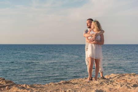 Mladý pár stojící na skalnatém mořském břehu při pohledu na zapadající slunce. Muž objímající ženu.