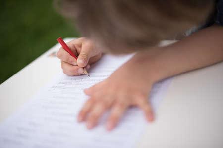 소년의 손을 자신의 노트북에 빨간색 연필로 작성합니다. 그의 손 및 연필에 초점을 맞춘 필드의 매우 얕은 깊이. 스톡 콘텐츠