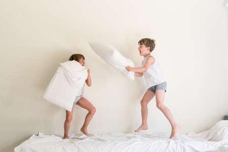 작은 아이들은 침대에 점프와 베개와 싸우는 재미