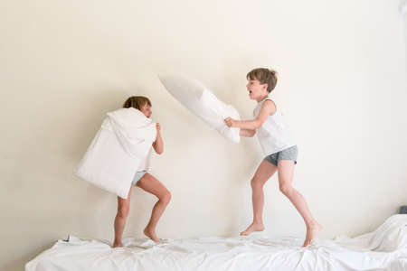 Small children jumping on a bed and having fun fighting with pillows Reklamní fotografie - 81410066