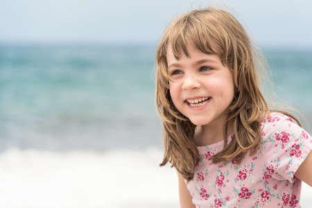 해변에서 놀고있는 동안 웃는 긴 금발 머리를 가진 행복한 소녀 스톡 콘텐츠