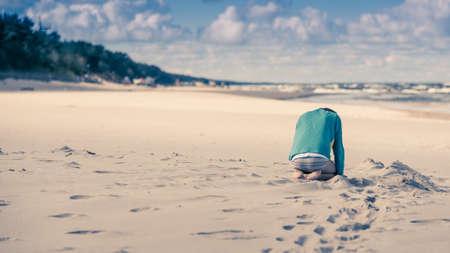 작은 슬픈 자식 머리와 모래 해변에 혼자 앉아
