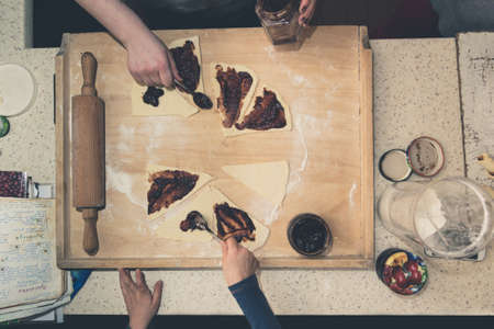 Top down shot on a wooden board where two people prepare crescent rolls for baking Reklamní fotografie