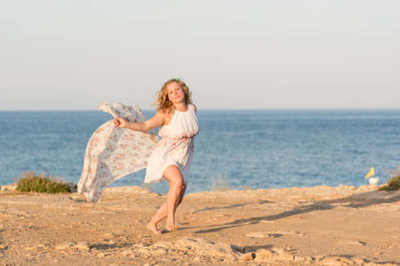 Young beautiful blond woman wearing white short dress dancing on a rocky sea shore with long scarf