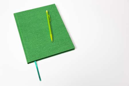 흰색 배경에 고립 된 닫힌 된 일정 책에 누워 녹색 연필