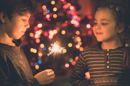 Young siblings, boy and girl looking at burning sparklers in the christmas eve evening with blurred christmas tree in background