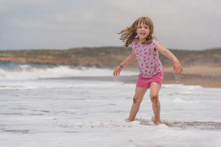 바다 파도 놀고있는 동안 웃는 작은 소녀