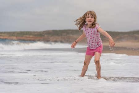 Kleines Mädchen lächelnd beim Spielen mit Seewellen