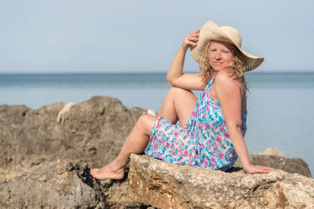 Young long blond hair woman wearing straw hat sitting on a rocks at sea Standard-Bild