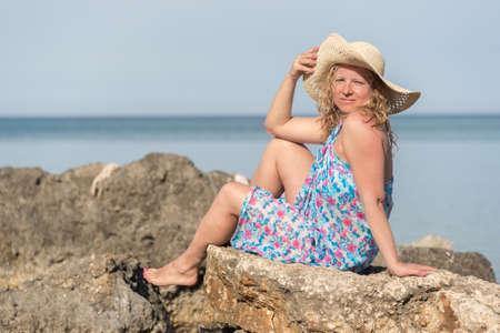 Mladá žena s dlouhými blond vlasy na sobě stojící klobouk sedí na skalách na moři
