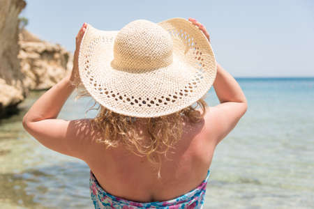 Young woman with long blond hair wearing straw hat and looking at sea
