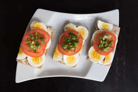 Three small sandwiches with egg, slices of tomateo and chopped chive on a white plate Reklamní fotografie