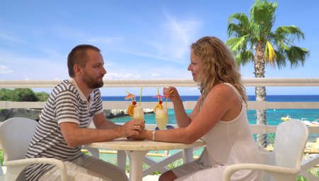 Young couple having colorful cocktail drinks at a sea side restaurant with palm tree and sea bay in background