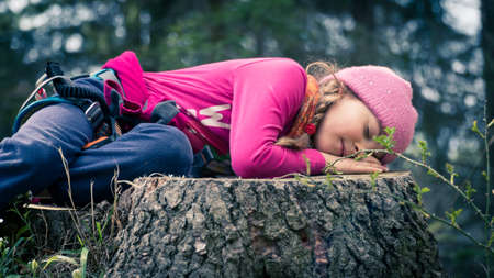 Cute little girl wearing purple blouse and pink hat sleeping on a cut tree trunk in a forest 스톡 콘텐츠